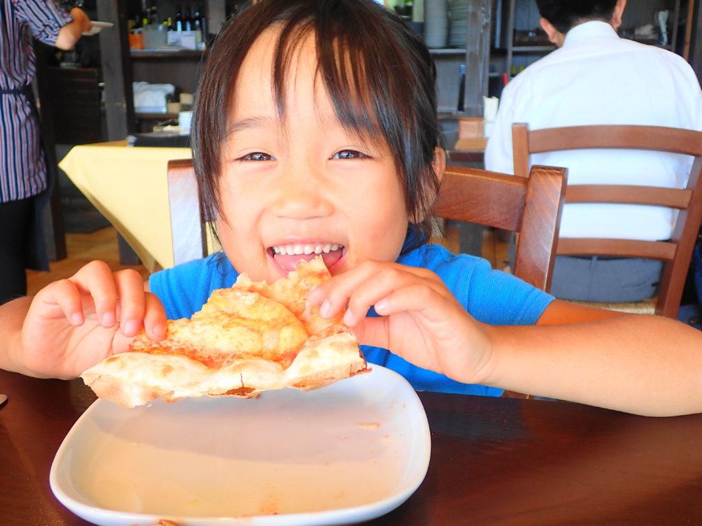 美味しそうにピザを食べる娘
