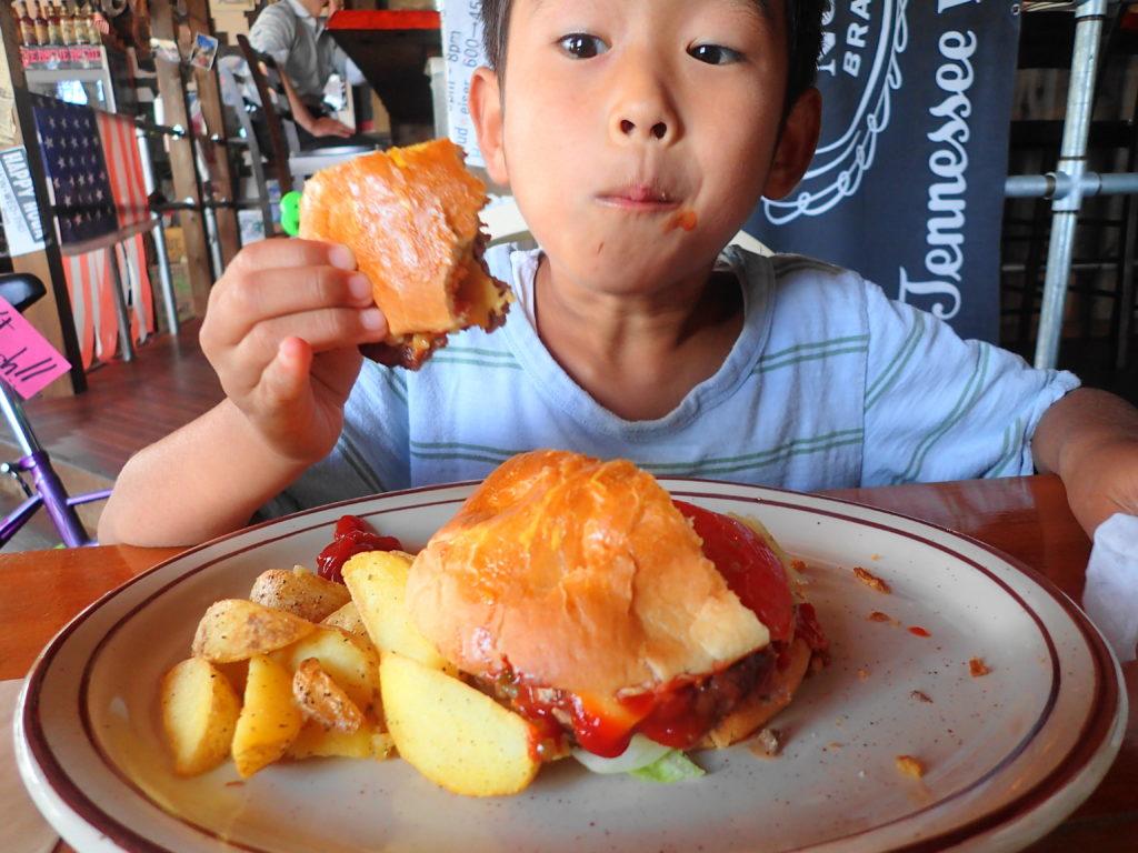 ハンバーガーを夢中で食べる息子