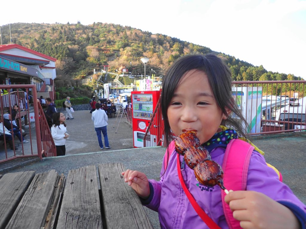 筑波山で団子を食べる娘
