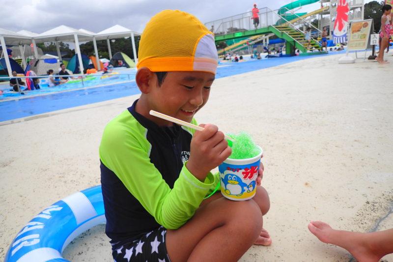 プールサイドでかき氷を食べる子