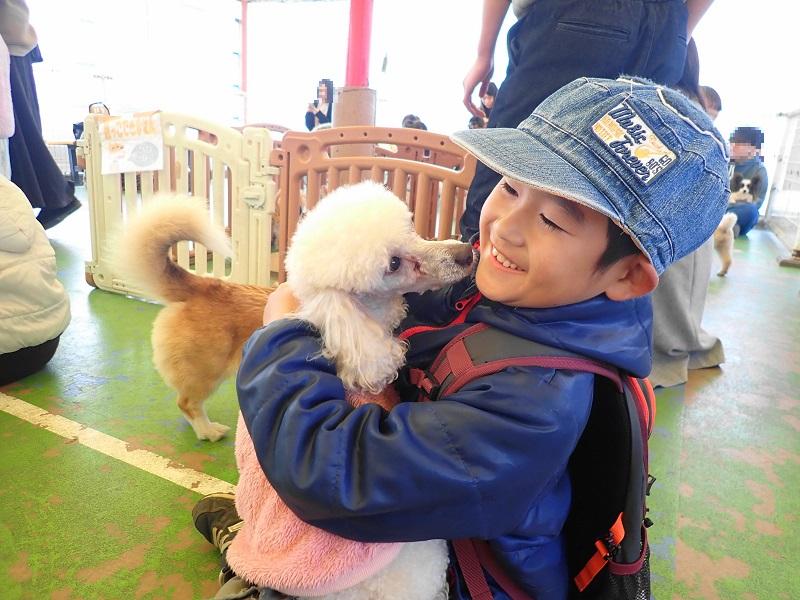 犬を抱っこして笑顔の息子